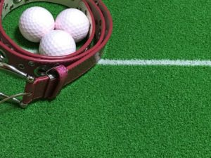 ゴルフボールとオシャレなベルトの画像