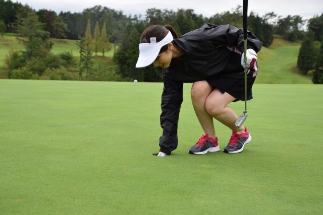 レインウェアを着た女性ゴルファー